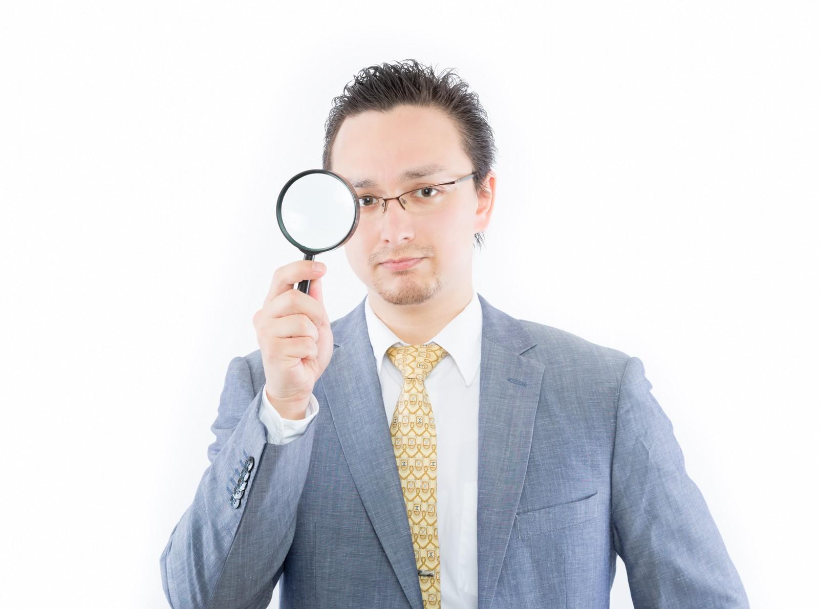 虫めがねを持ってる男性の画像